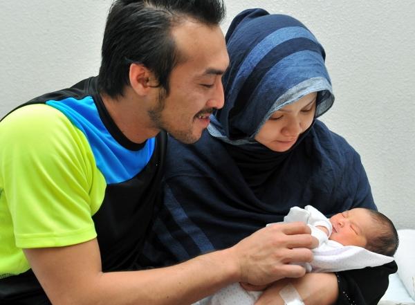 Khairul Fahmi (kiri) dan Leuniey tersenyum gembira memerhatikan gelagat bayi perempuan mereka.