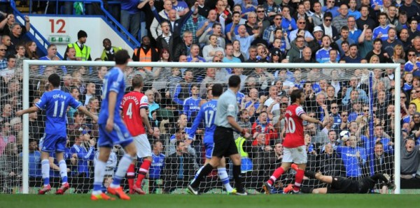 Chelsea's Brazilian midfielder Oscar (L) scores his team's fifth goal during the English Premier League football match between Chelsea and Arsenal at Stamford Bridge in London on March 22, 2014. Chelsea won 6-0. AFP PHOTO / GLYN KIRK