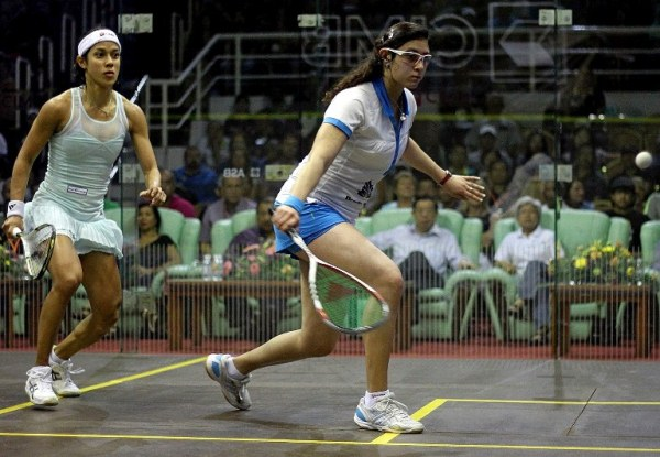 Egypt's Nour El Sherbini (R) plays a return shot against Nicol David of Malaysia (L) during their CIMB Women's World Championship semi-final match at the Spice Arena on March 22, 2014 in Georgetown. Unseeded Egyptian Nour El Sherbini pulled off the biggest upset of the world women's championship  by beating defending world champion Nicol David 4-11, 11-9, 11-6, 2-11, 11-9 in front of 2,000 shell-shocked fans in her hometown.       AFP PHOTO