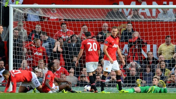 Manchester United's Spanish goalkeeper David de Gea (Far R) reacts after the Southampton goal by Croatian footballer Dejan Lovren during the English Premier League football match between Manchester United and Southampton at Old Trafford in Manchester, north-west England, on October 19, 2013. AFP PHOTO/ANDREW YATES  RESTRICTED TO EDITORIAL USE. No use with unauthorized audio, video, data, fixture lists, club/league logos or ?live? services. Online in-match use limited to 45 images, no video emulation. No use in betting, games or single club/league/player publications.