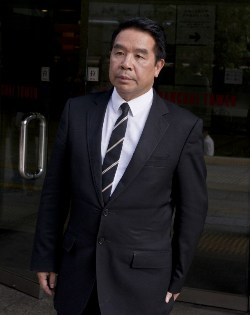 Hairdresser-turned-football tycoon, Birmingham City owner Carson Yeung leaves the Wanchai district court in Hong Kong on October 28, 2013. Yeung has insisted he amassed his fortune through legitimate means, including high-end hair salons, as he testified in his 93 million USD money-laundering trial in Hong Kong.  AFP PHOTO / ALEX OGLE