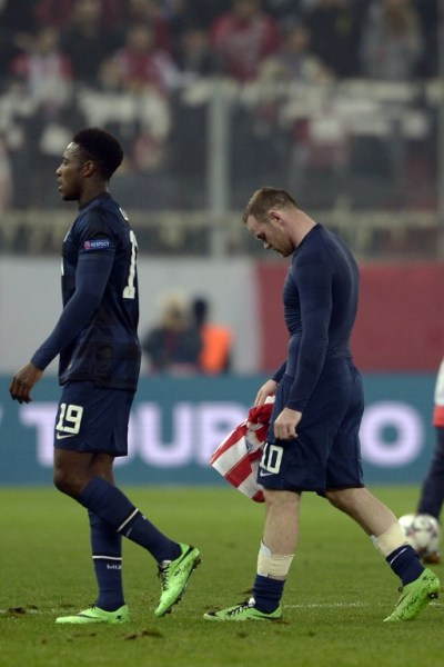 Manchester United's English forward Wayne Rooney (R) and English forward Danny Welbeck walk off the pitch after losing the round of 16 Champions League football match Olympiakos vs Manchester United at Karaiskaki Stadium in Athens on February 25, 2014. AFP PHOTO / ARIS MESSINIS