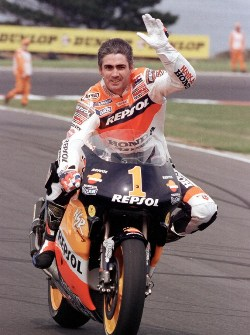 Reigning five-time World Champion Mick Doohan of Australia waves to fans during a lap of honour before the start of the 1999 Australian 500cc Motorcycle Grand Prix on Phillip Island 03 October 1999.  Doohan was unable to race due to injures sustained on the first day of the Spanish Grand Prix in Jerez in May.  AFP PHOTO/Nigel PATERSON