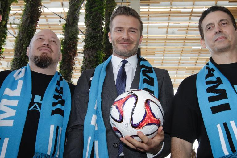 Former football star David Beckham (C), wearing a Major League Soccer scarf, posing with MLS fans at the Perez Art Museum in Miami, Florida, on February 5, 2014 (AFP Photo/Alexia Fodere)