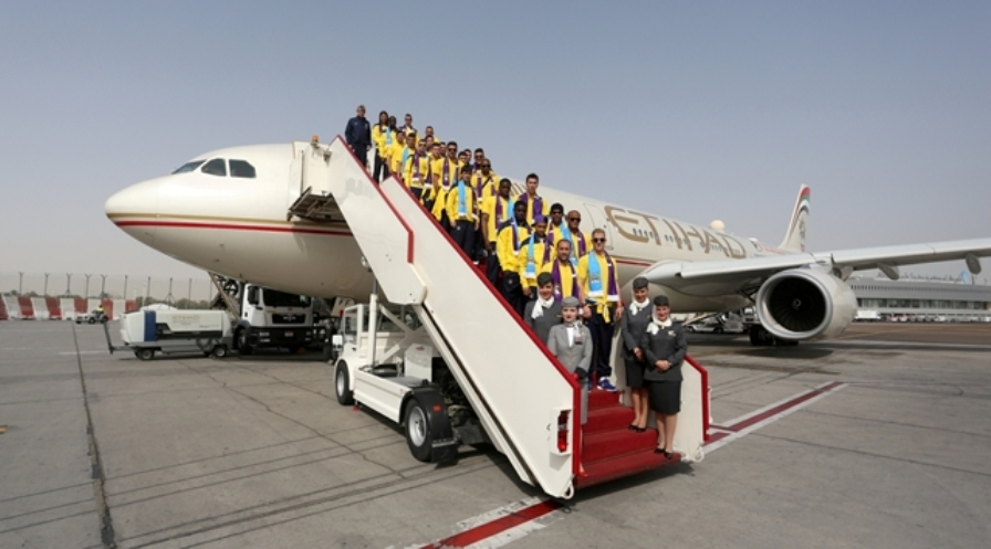 Manchester City players and officials board the Etihad Airways flight to Abu Dhabi