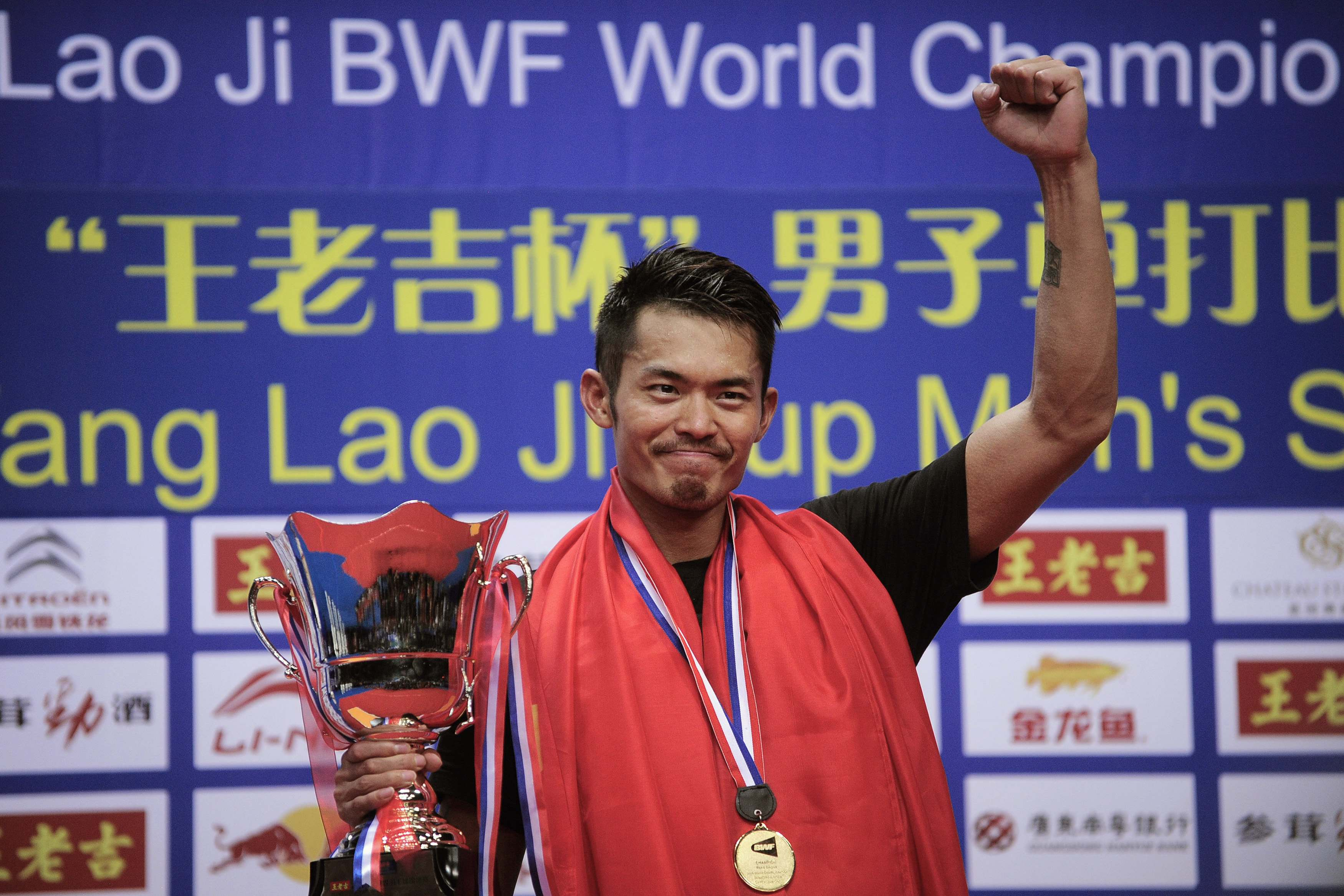 China's Lin Dan gestures with his trophy on the podium after defeating Malaysia's Lee Chong Wei during their men's singles final match at the 2013 Badminton World Championships in Guangzhou, Guangdong province August 11, 2013. REUTERS/Stringer