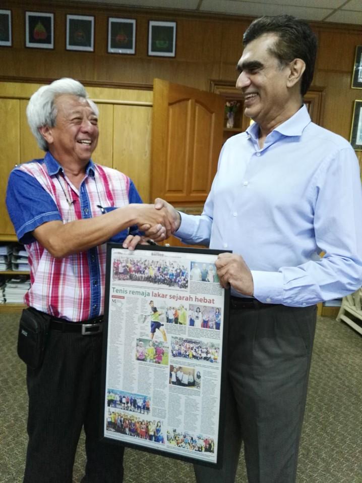 Datuk Sam Mannan receiving the framed newspaper.