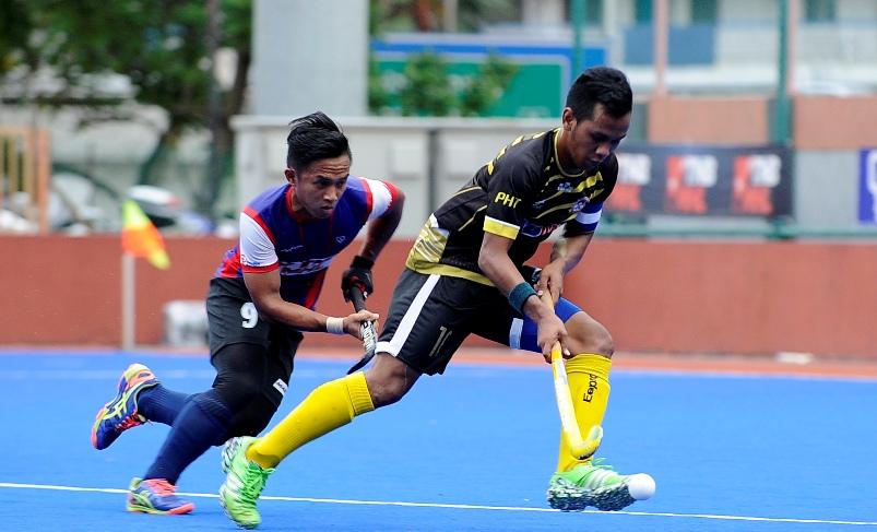 Pemain THT, Faizal Shaari cuba melepasi kawalan pemain TNB Shahril Izwan dalam aksi separuh akhir yang dimenangi TNB 3-2